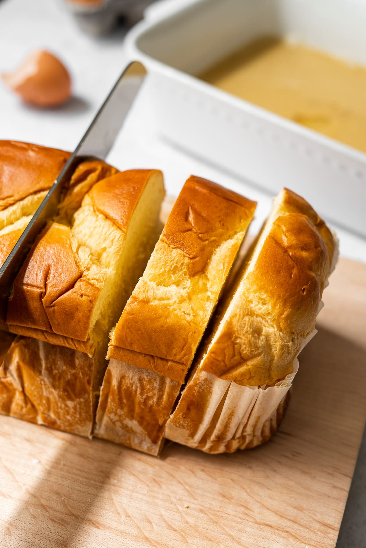 cutting thick cut slices from a brioche bread loaf