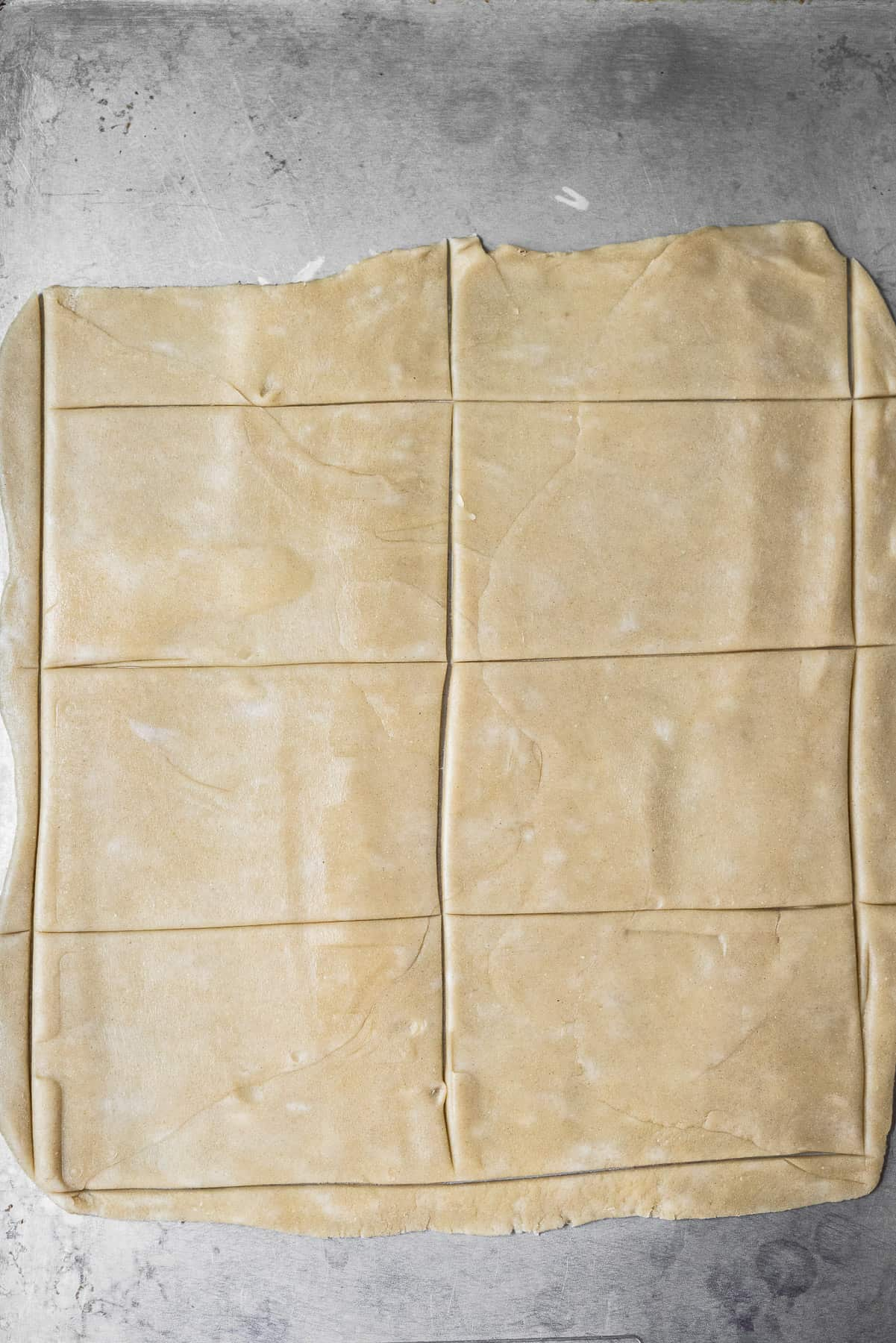 cutting out rectangles in pie dough on a sheet tray