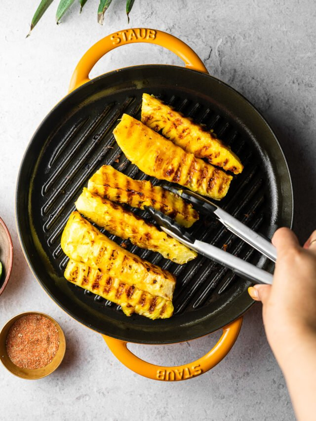 using tongs to flip grilled pineapple spears on a staub grill pan