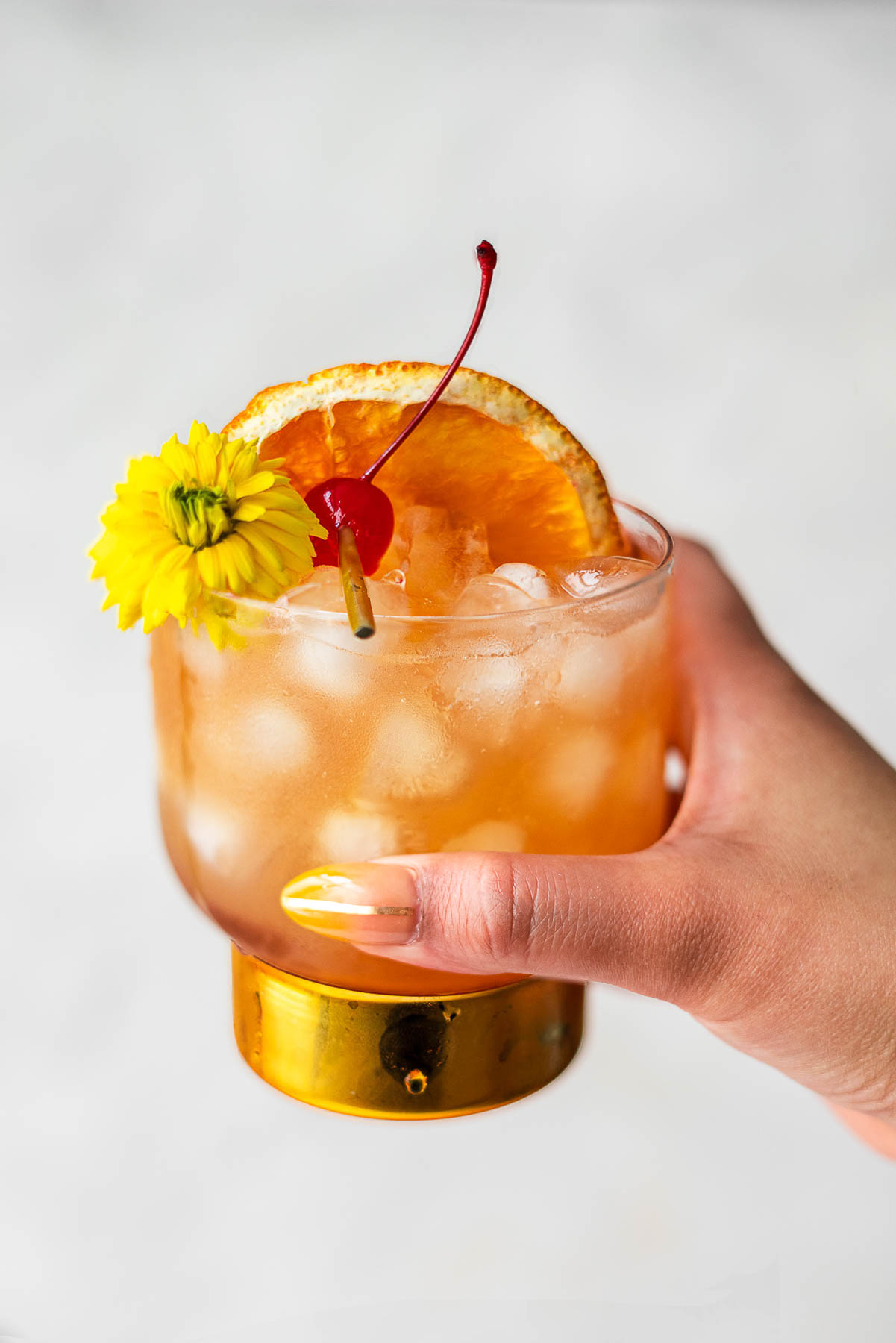 Manicured hand holding up a cup with amaretto sour with a gold bottom and cherry, flour, and orange slice as garnish