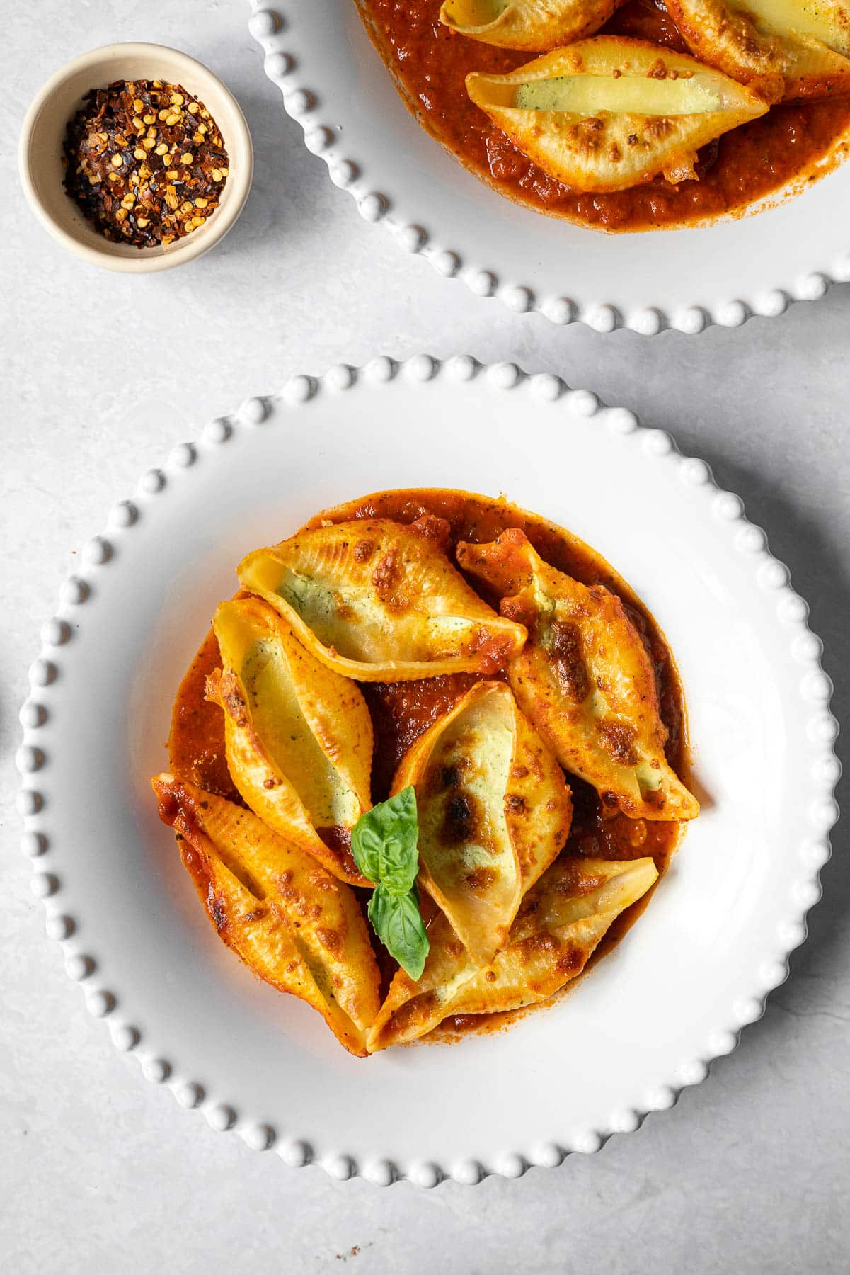 two bowls of Jumbo Pasta Shells with a Lemon Basil Ricotta Filling, browned mozzarella, set in tomato basil sauce with a condiment bowl of chili flakes
