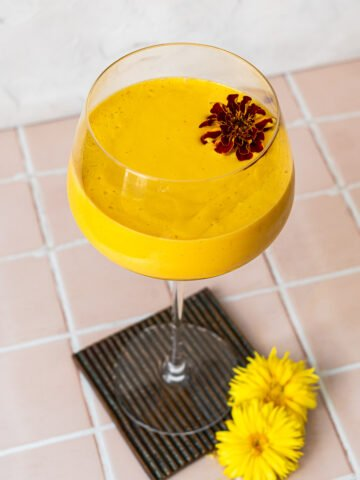 Mango Lassi with a marigold in a spritz glass on a coaster