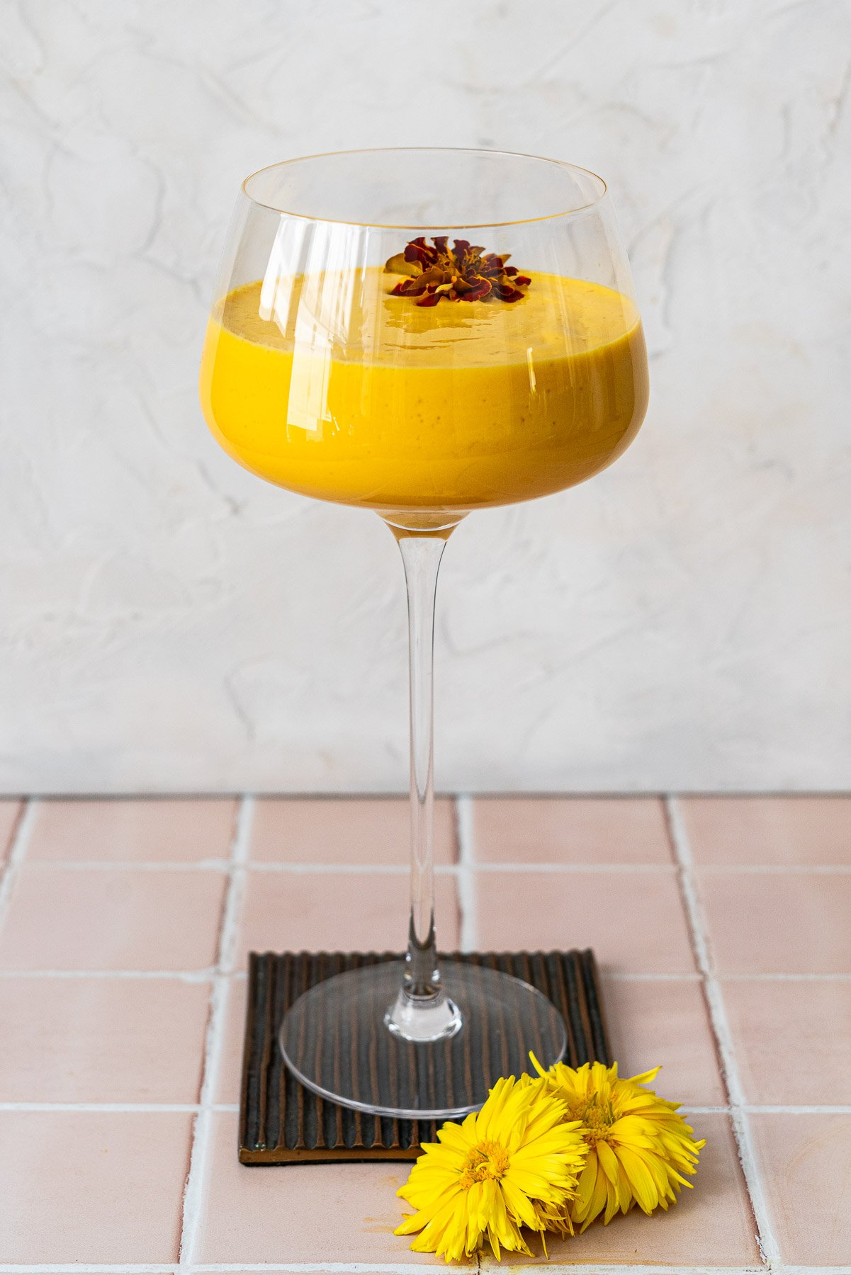 straight on shot of a mango lassi in a spritz glass on a coaster with edible flowers