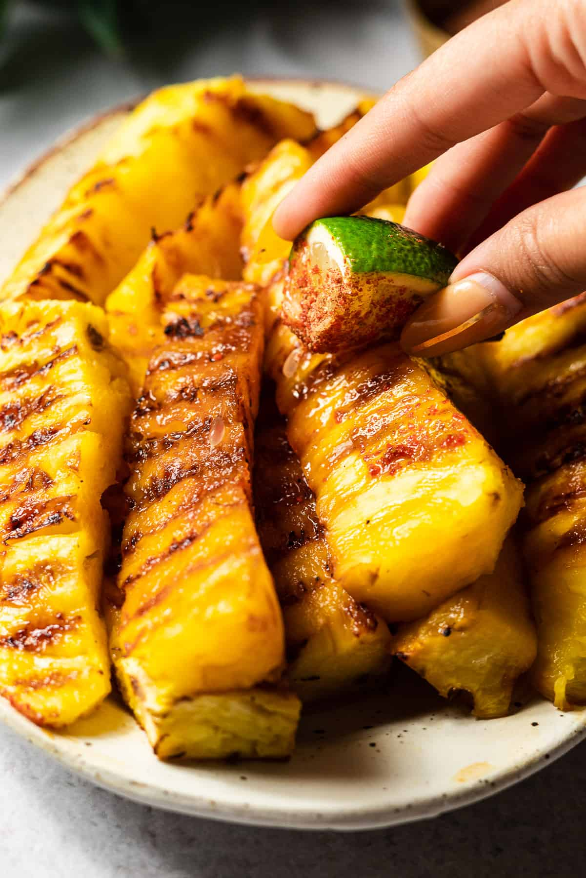 rubbing a lime on a grilled pineapple spear