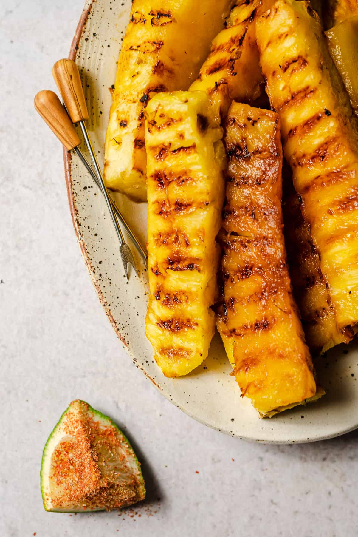 grilled pineapple in a platter with appetizer picks and a lime wedge covered with a seasoning blend