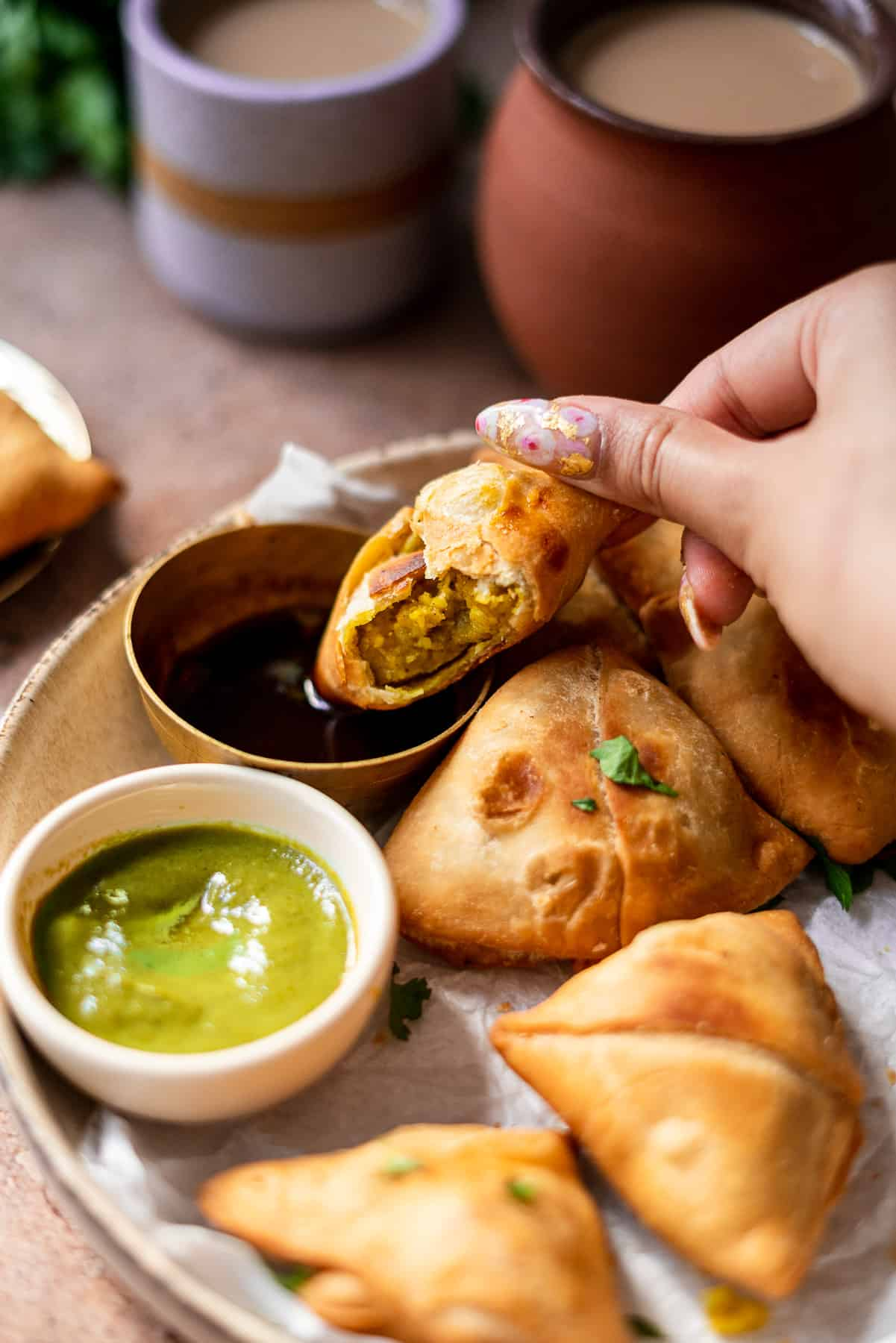 dipping a samosa in imli chutney with chai in the background