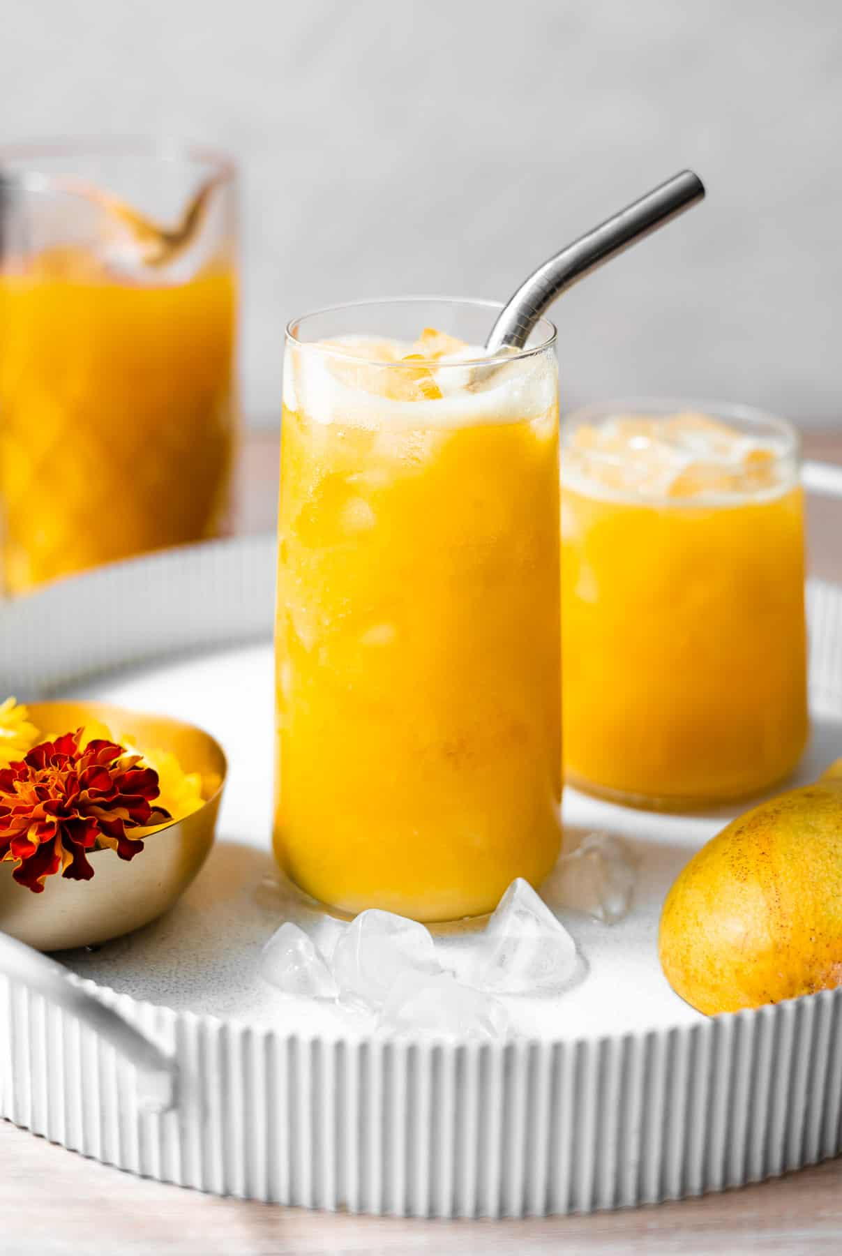 two sets of mango juice in glasses in a tray with flowers and fresh mangoes with a pitcher of mango juice