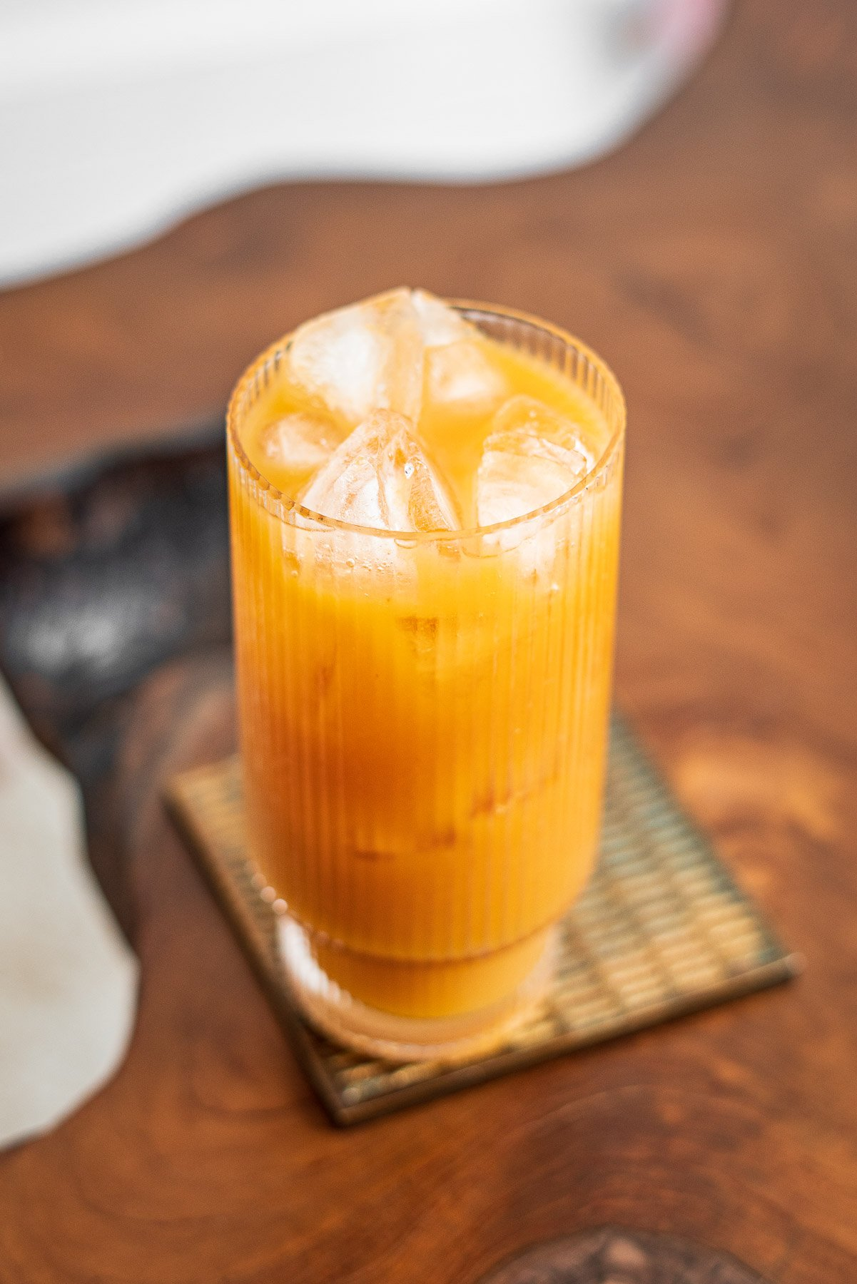iced mango tea in a tall glass on a wooden table