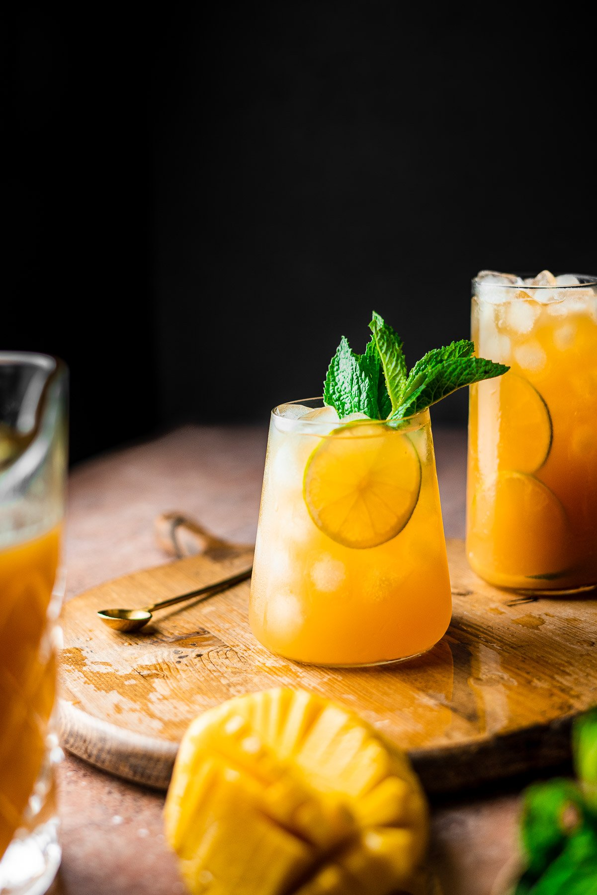 two glasses of mango iced tea with mint and lime slices on a wooden cutting board