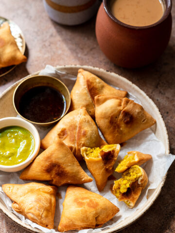 paneer aloo samosas in a bowl with chutneys and chai