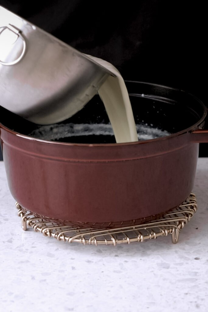 pulling the milk from a bowl into a pot