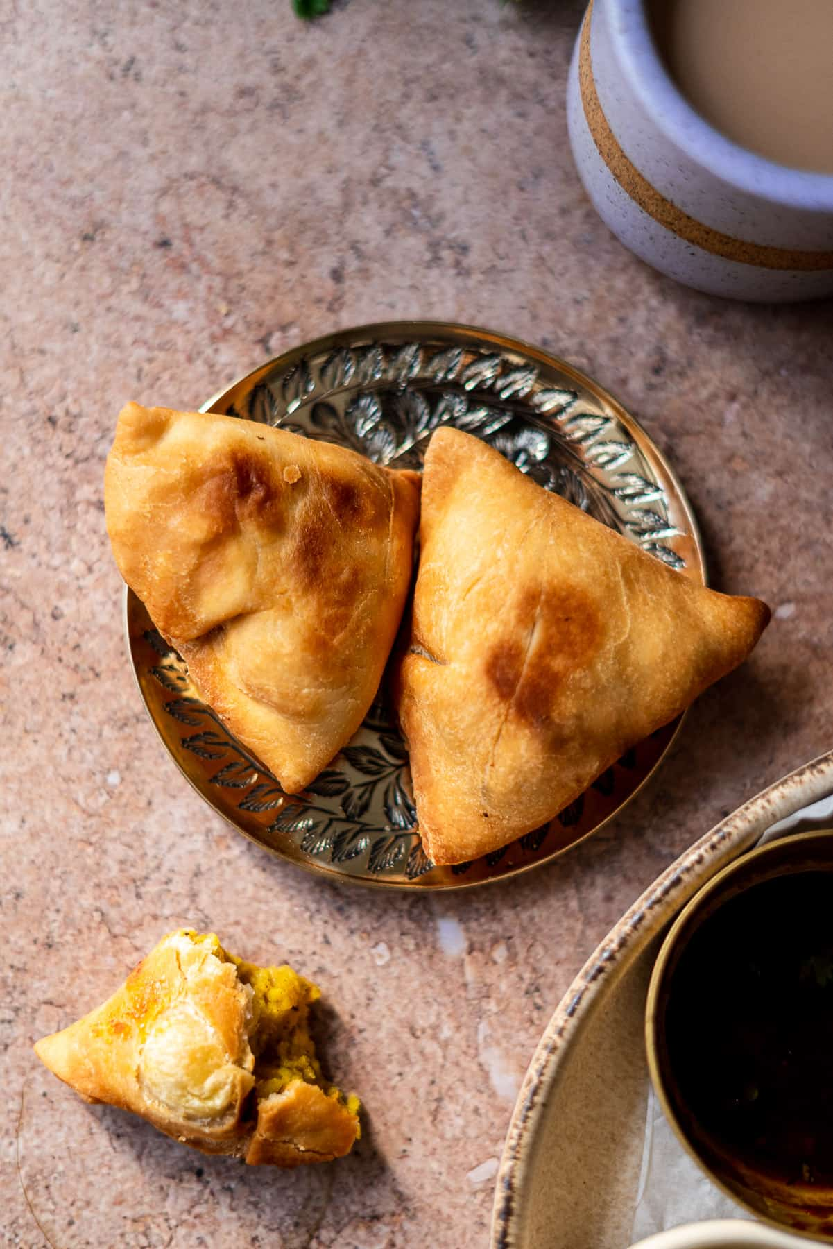 two samosas in a brass plate with a half eaten samosa