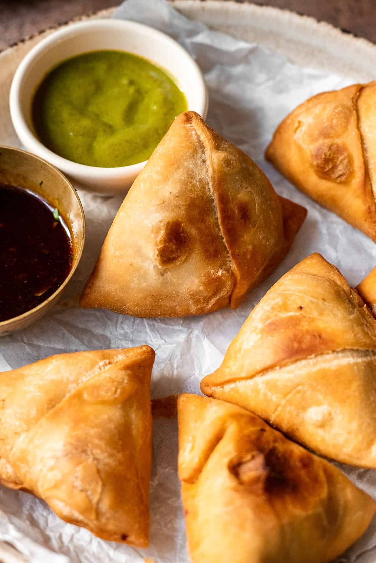 samosa in a plate propped up against chutneys