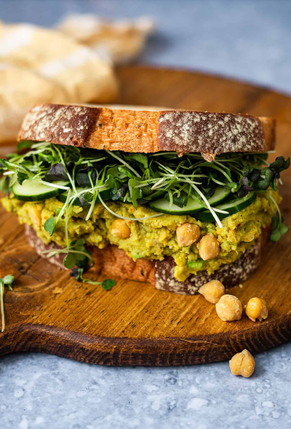 Smashed Chickpea and Avocado Sandwich Close up on a wooden board with chickpeas pieces