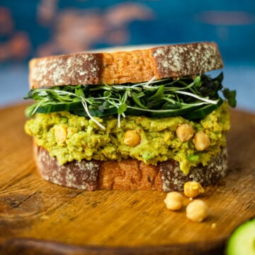 Smashed Chickpeas and Avocado Salad Sandwich on a wooden board