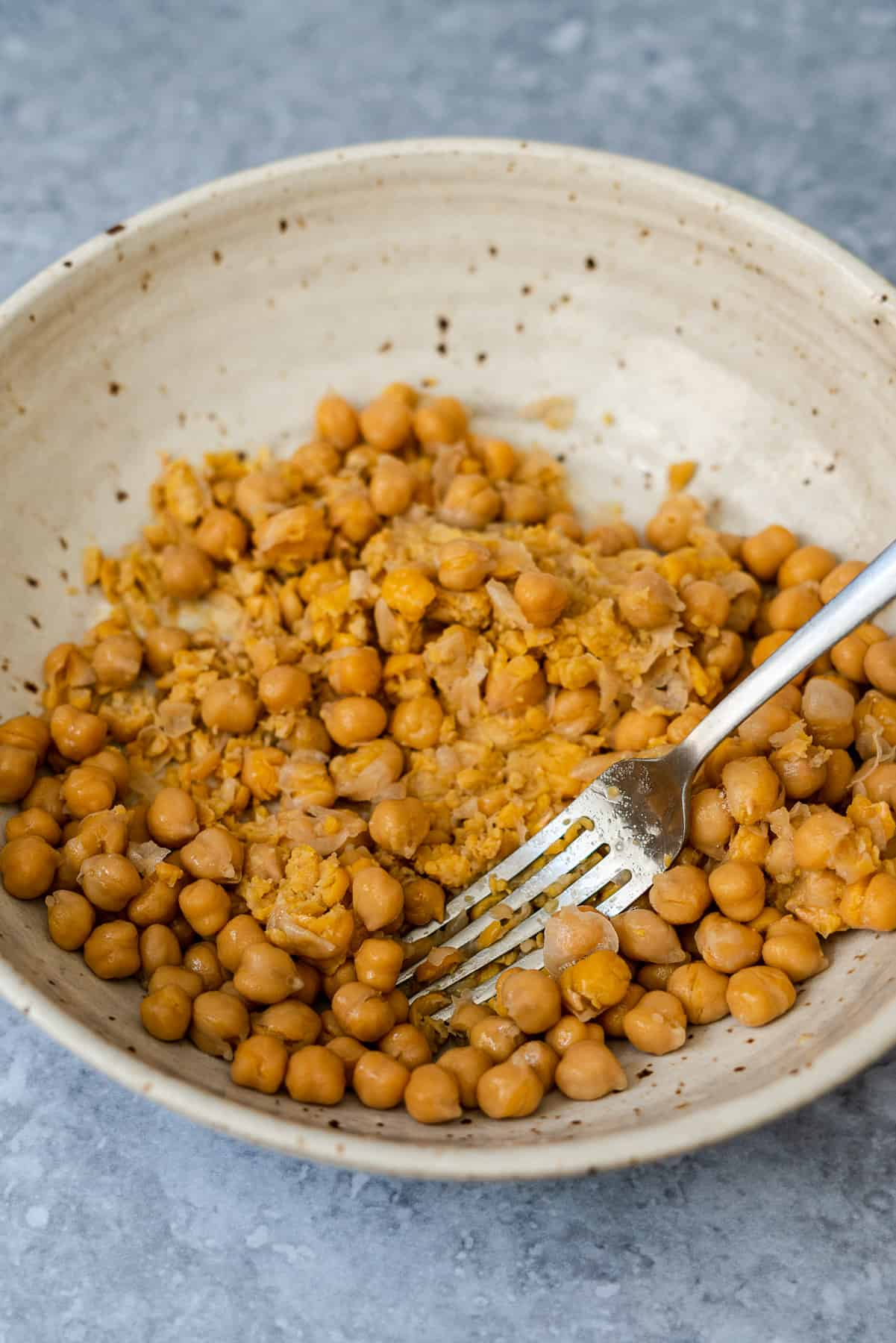 fork smashing cooked chickpeas in a bowl