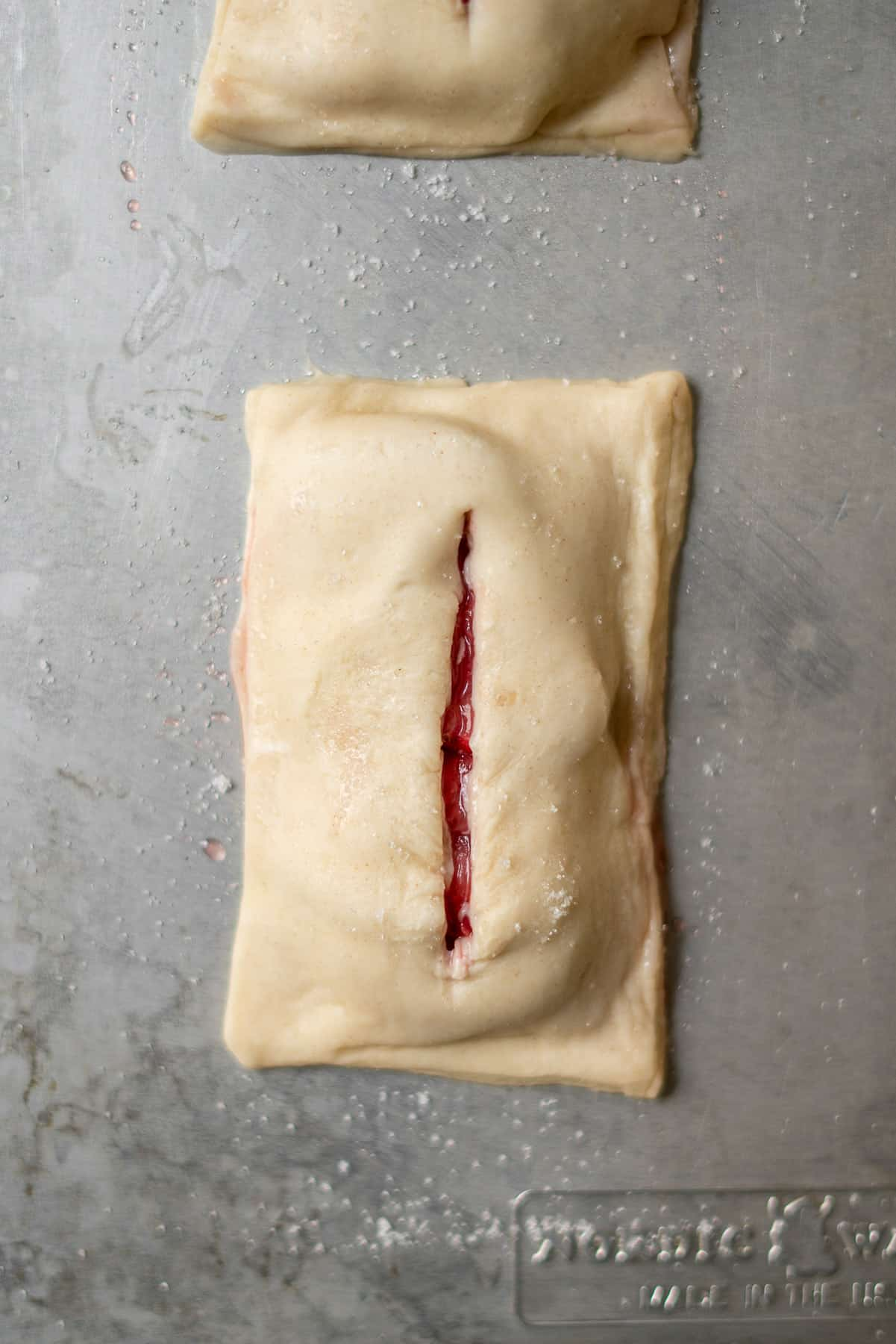 puff pastry sealed with a top layer with a slit down the middle revealing strawberries