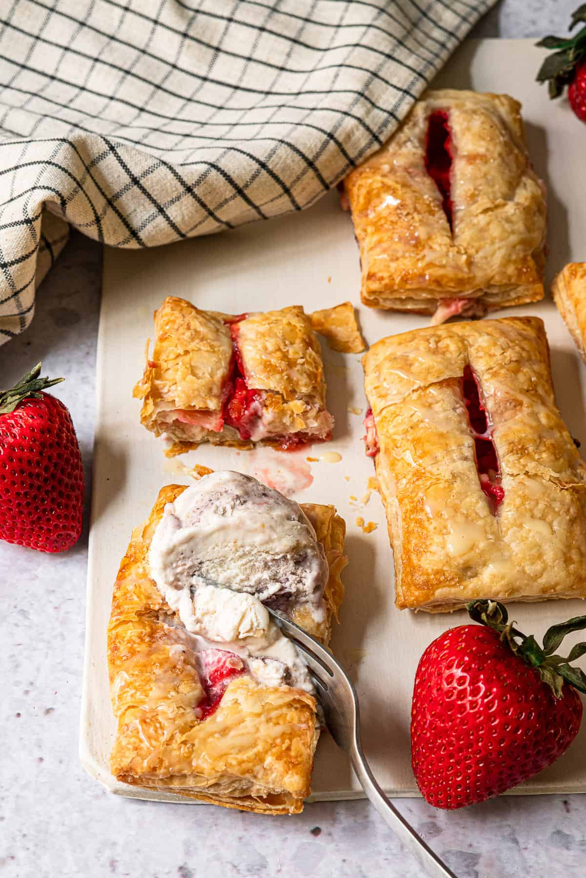 strawberry turnovers with a fork digging into a scoop of ice cream