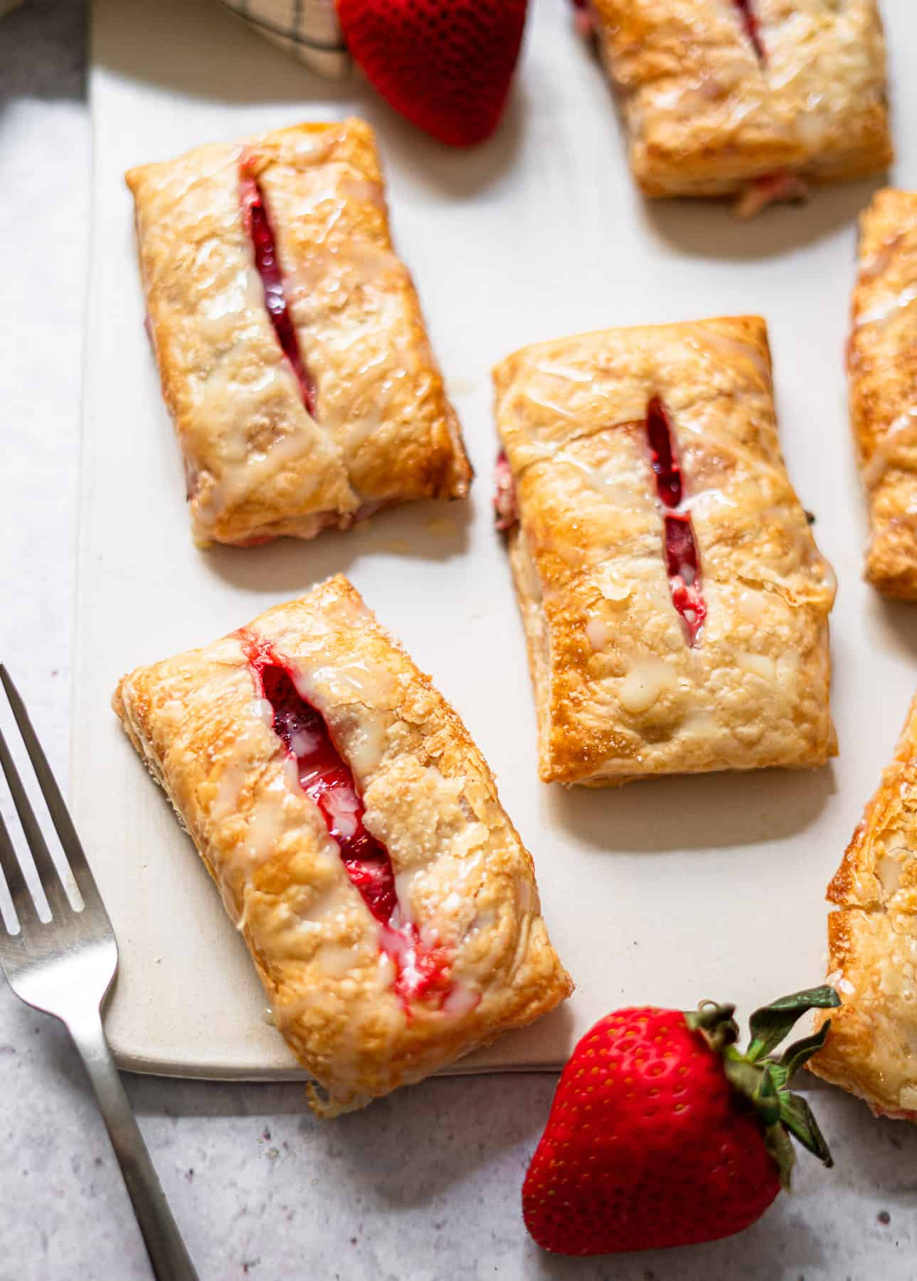 strawberry and cream cheese turnovers on a white board with fresh strawberries and a fork