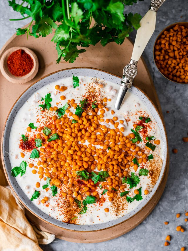 Boondi Raita in a big bowl with a serving spoon on a platter with chili powder, cilantro, and boondi