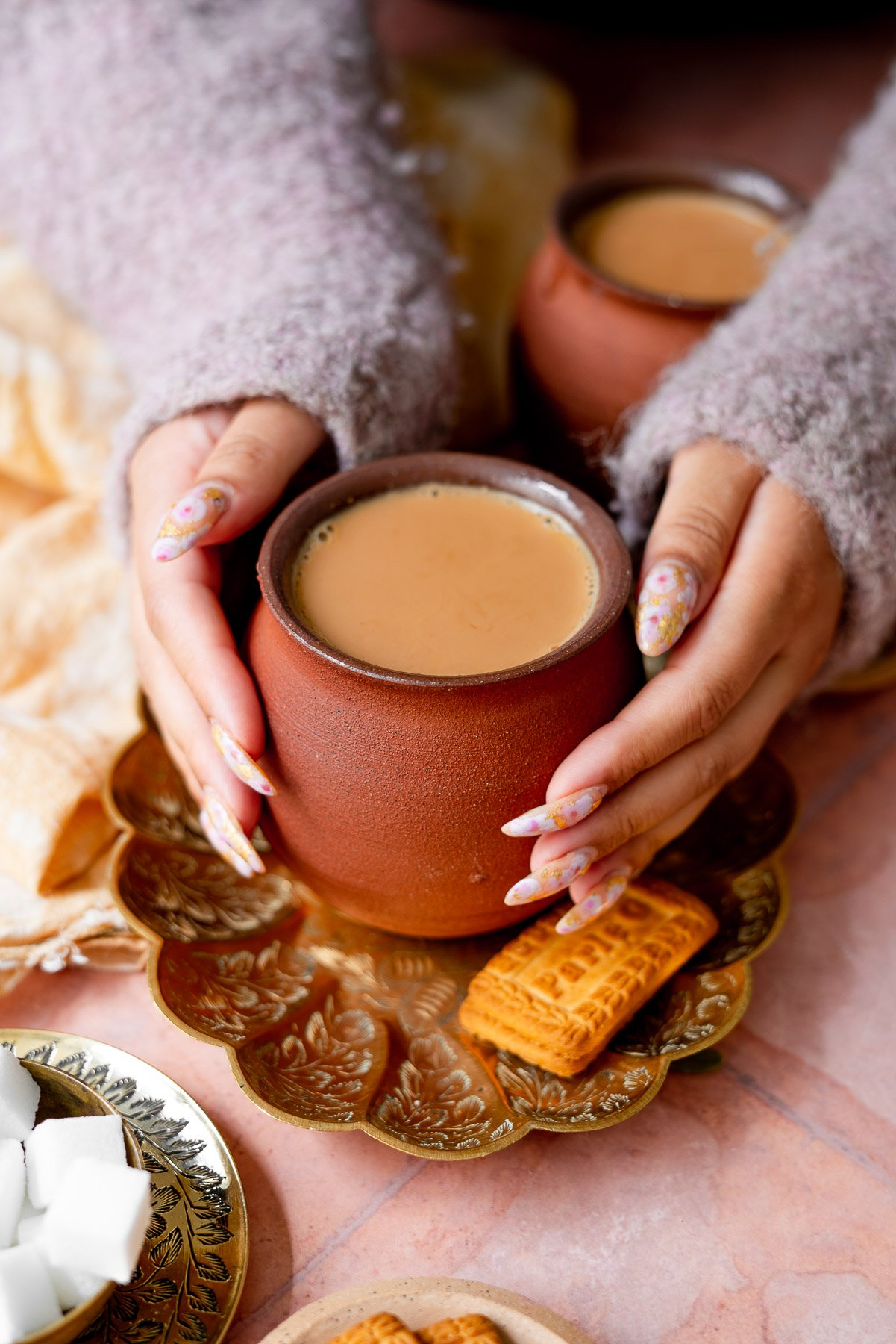 hands in a cozy sweater cozying with masala chai