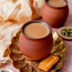 masala chai cups in a platter with sugar, parle g, and cardamom