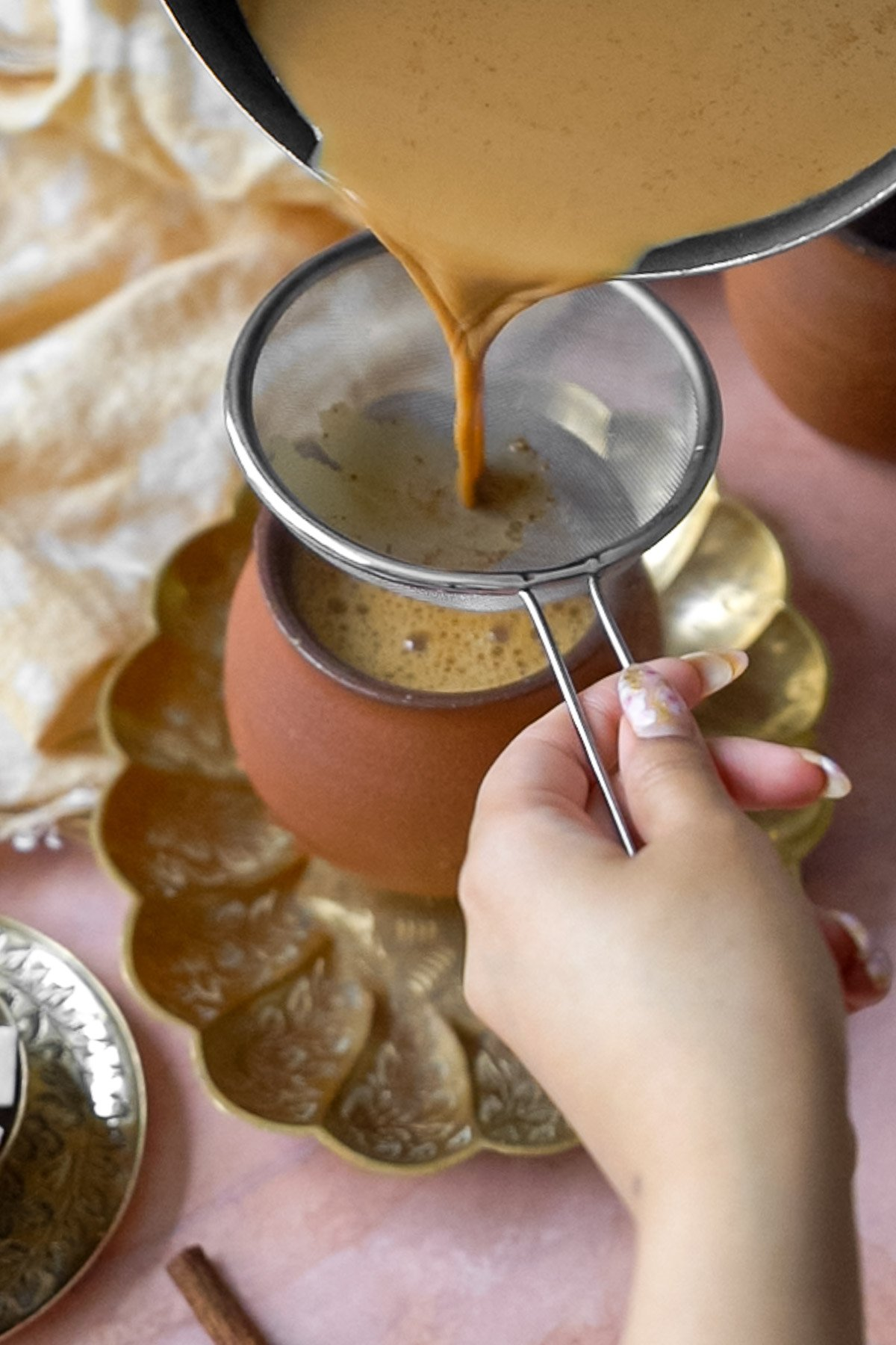pouring chai through a sieve into a cup