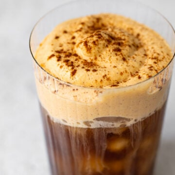cup with iced coffee and pumpkin cream cold foam on top