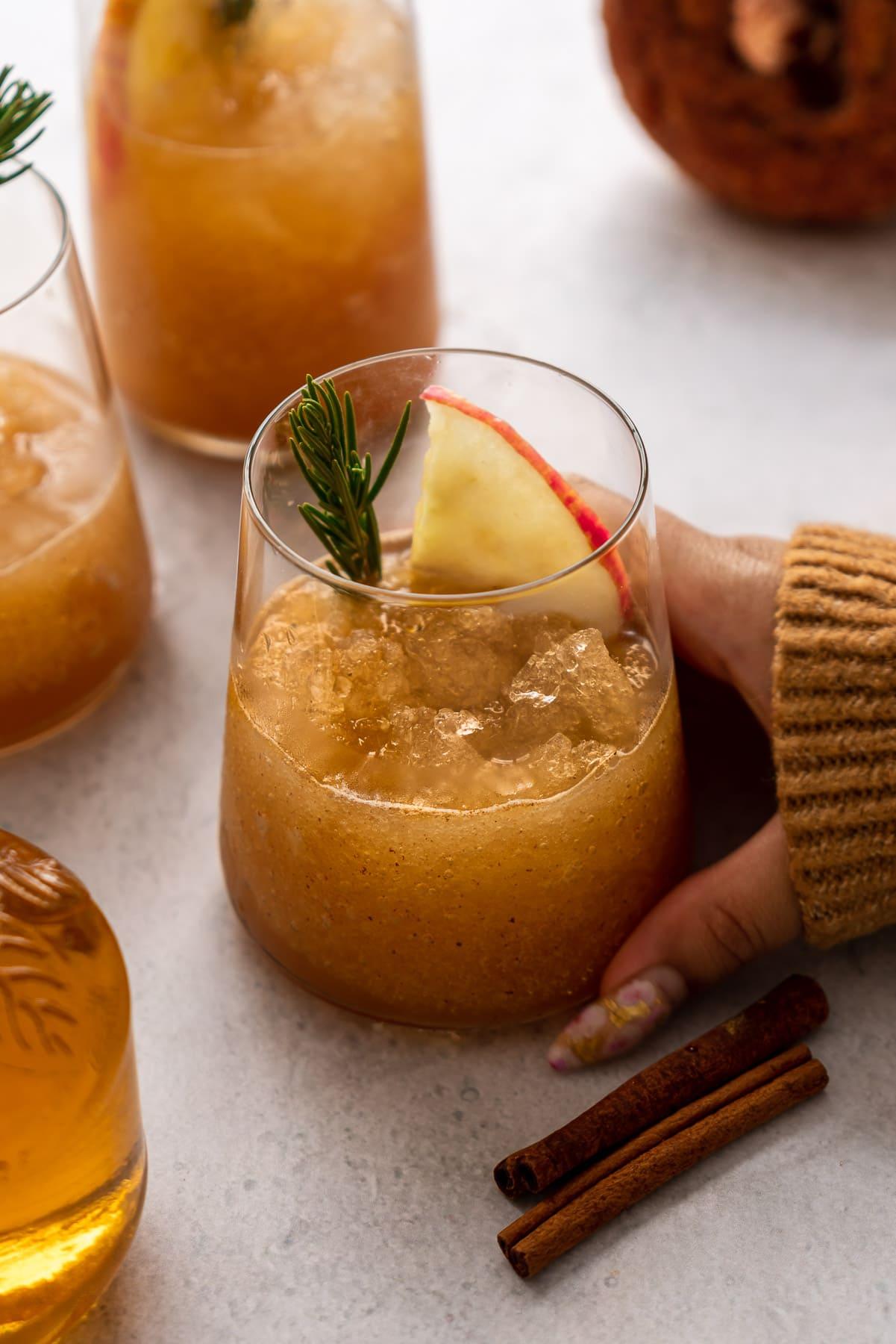 cozy hand holding a glass of apple cider slushie