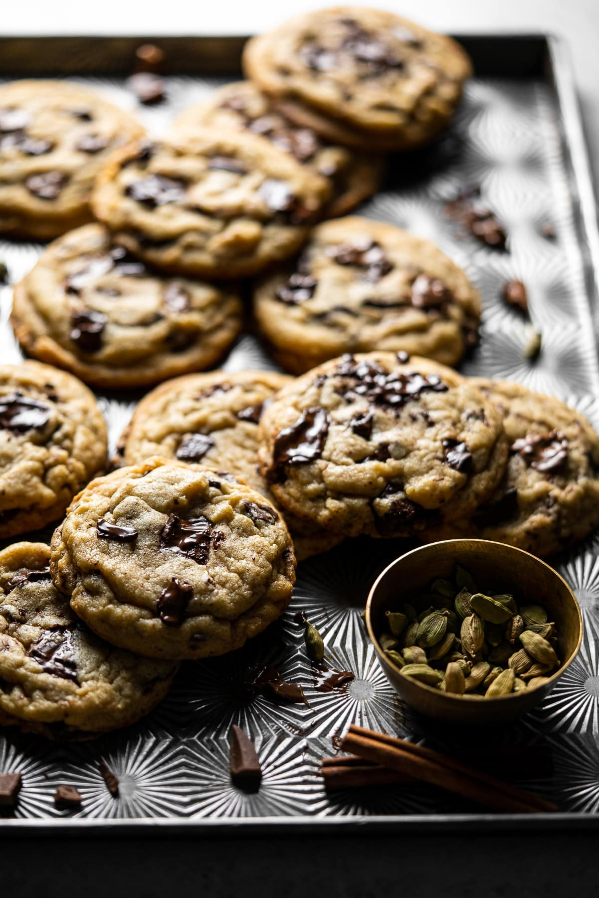 backlit tray with chocolate chip cookies and a bowl of cardamom