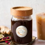 bottle of chai concentrate with a wood lid on a brass platter
