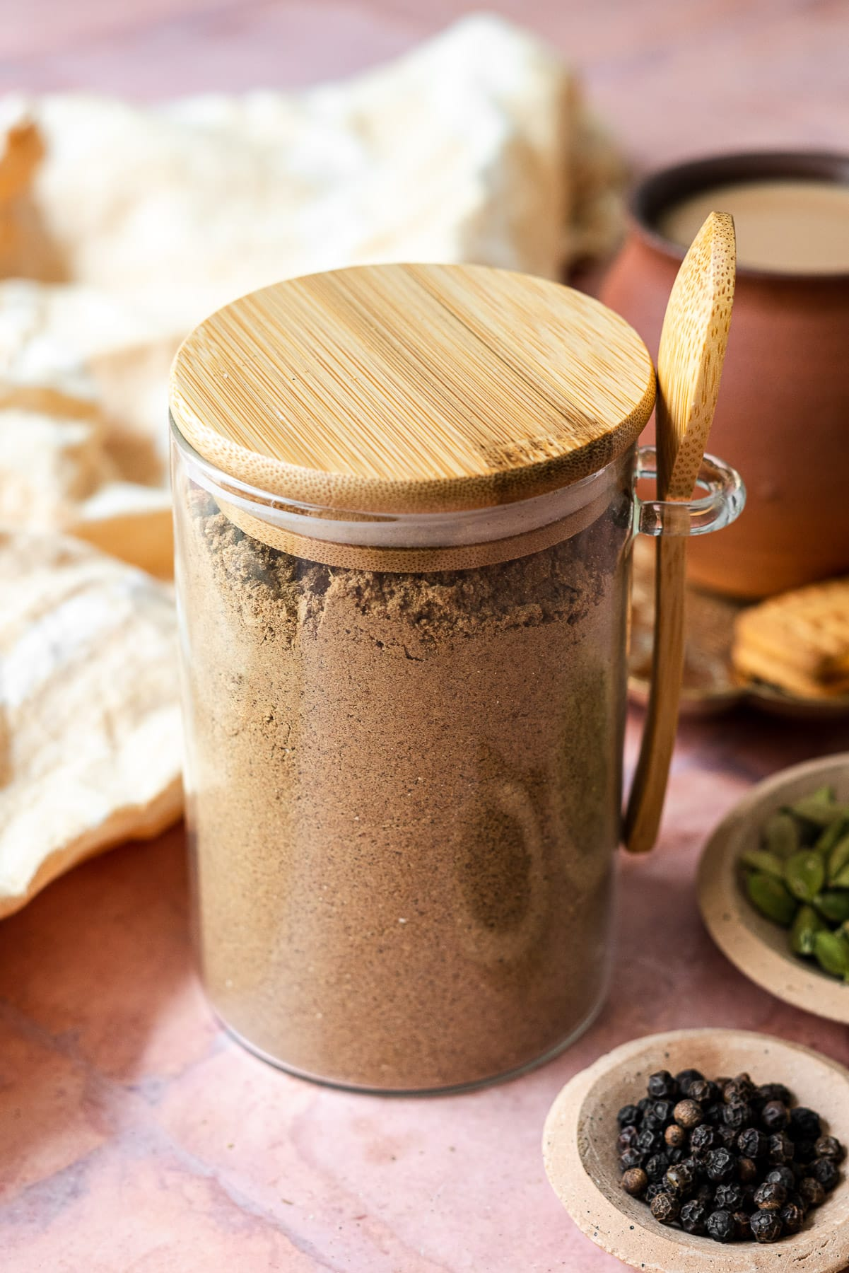 chai masala in a container with black pepper and cardamom seeds