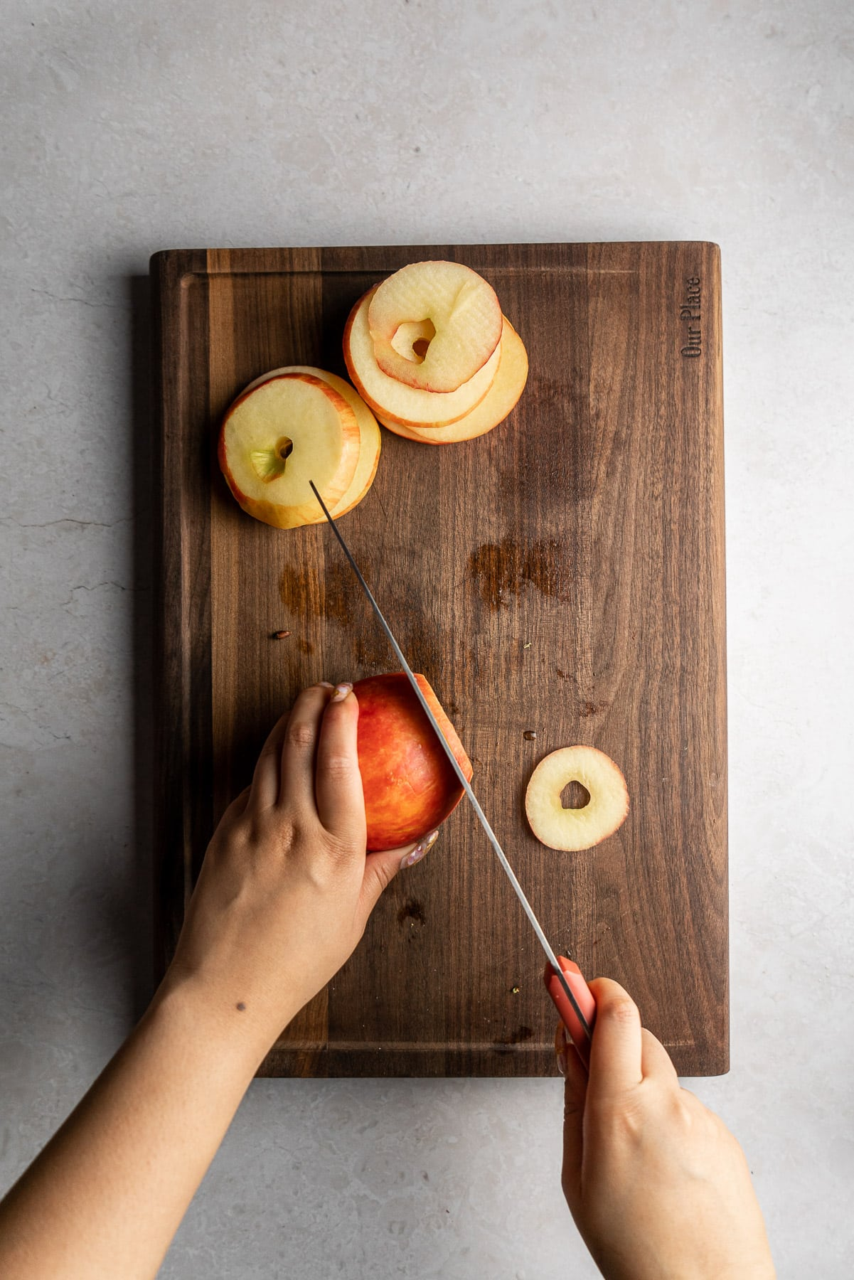 cutting honeycrisp apples into rings with a knife on a cutting board