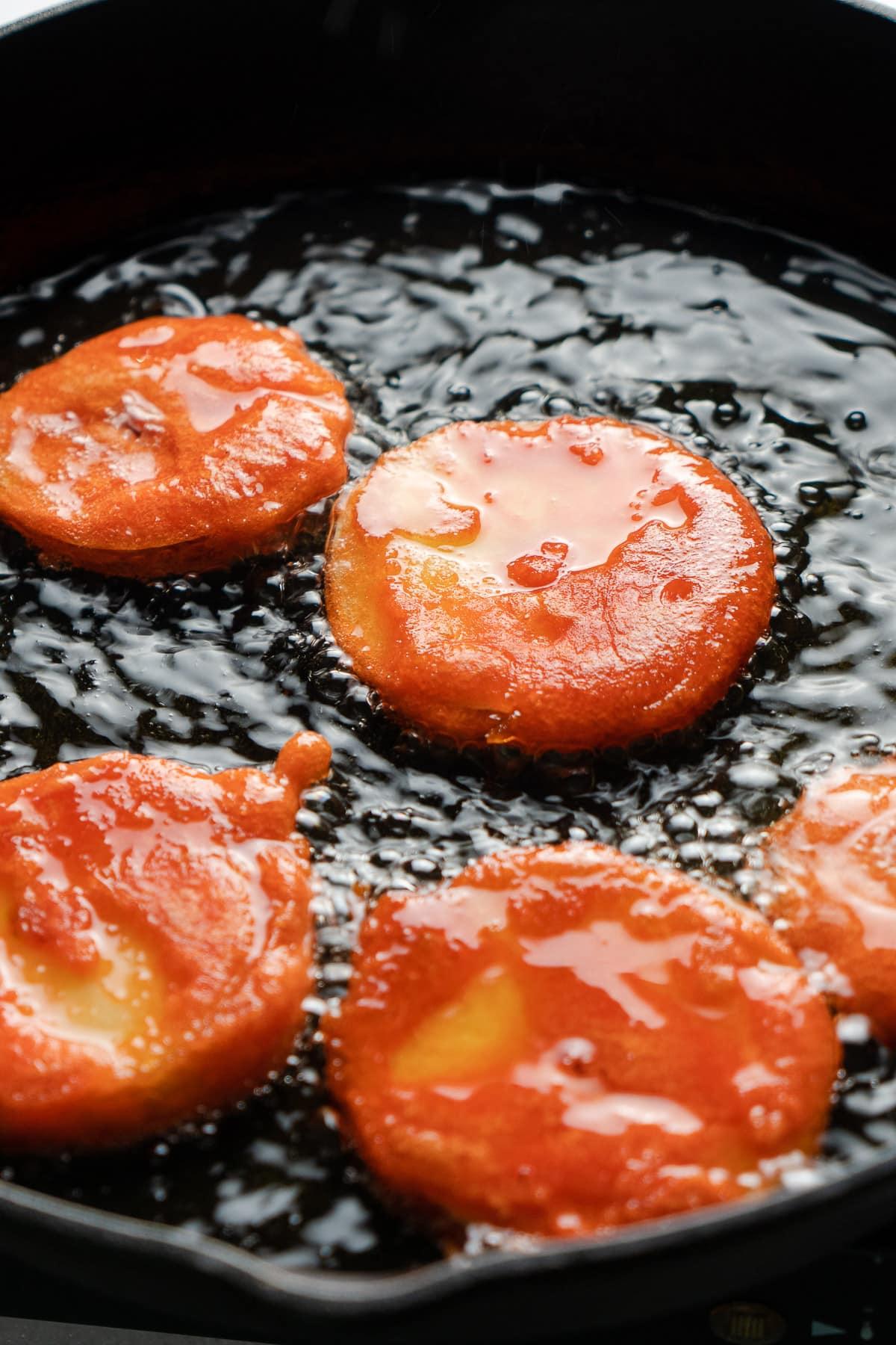 fried juicy apple jalebis in ghee in a skillet