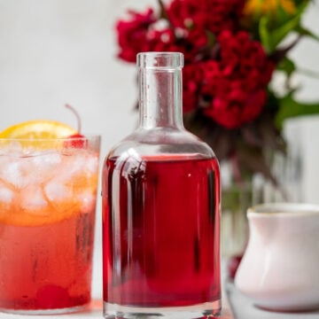 glass bottle with grenadine with a shirley temple and red flowers in the background