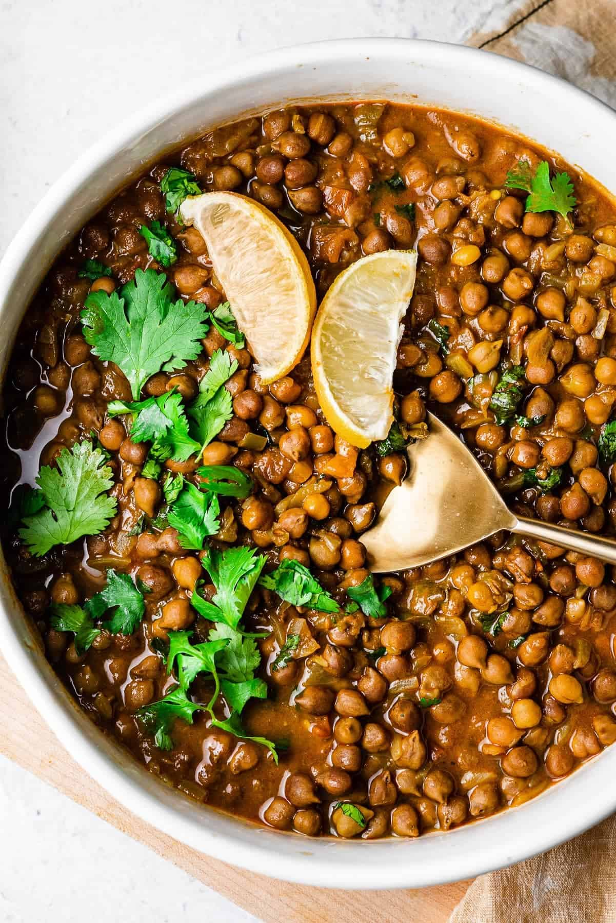 kala chana masala in a serving bowl with a gold serving spoon