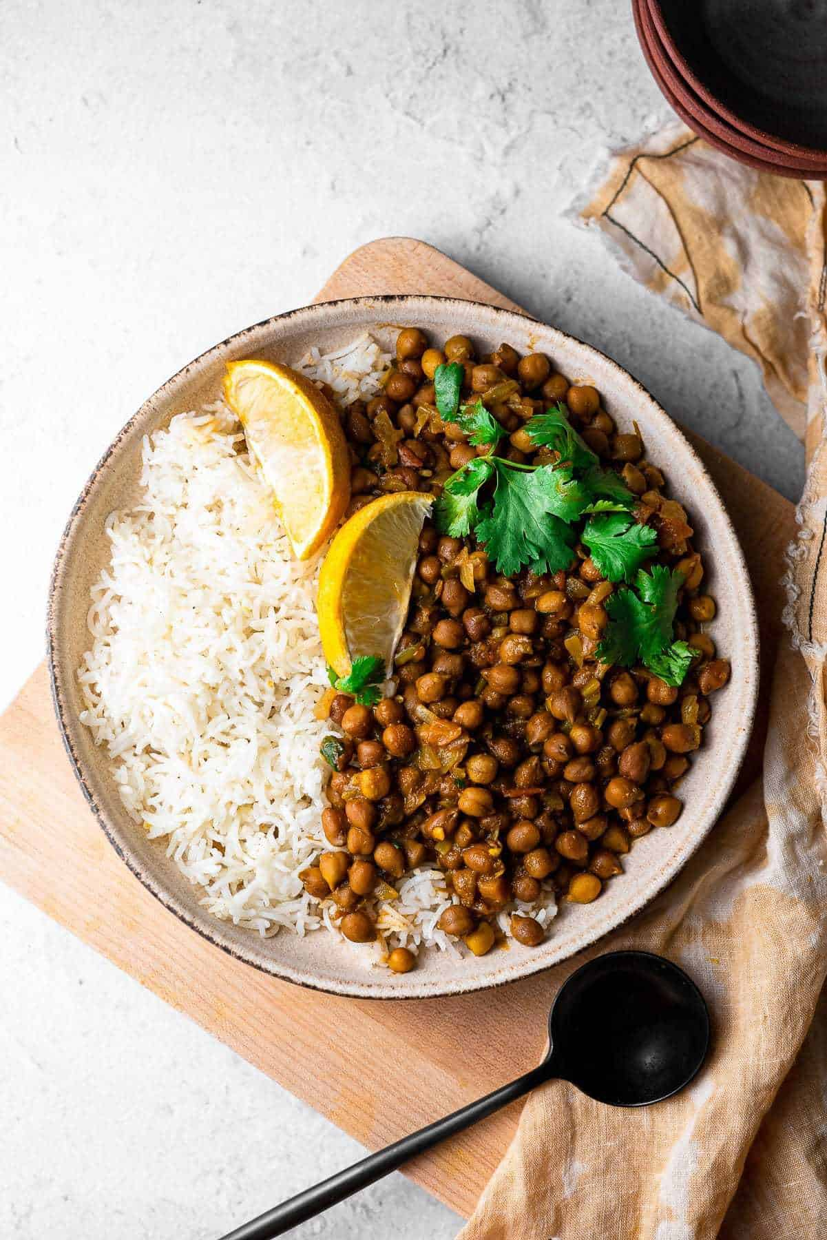 kala chana in a bowl with rice and lemon slices
