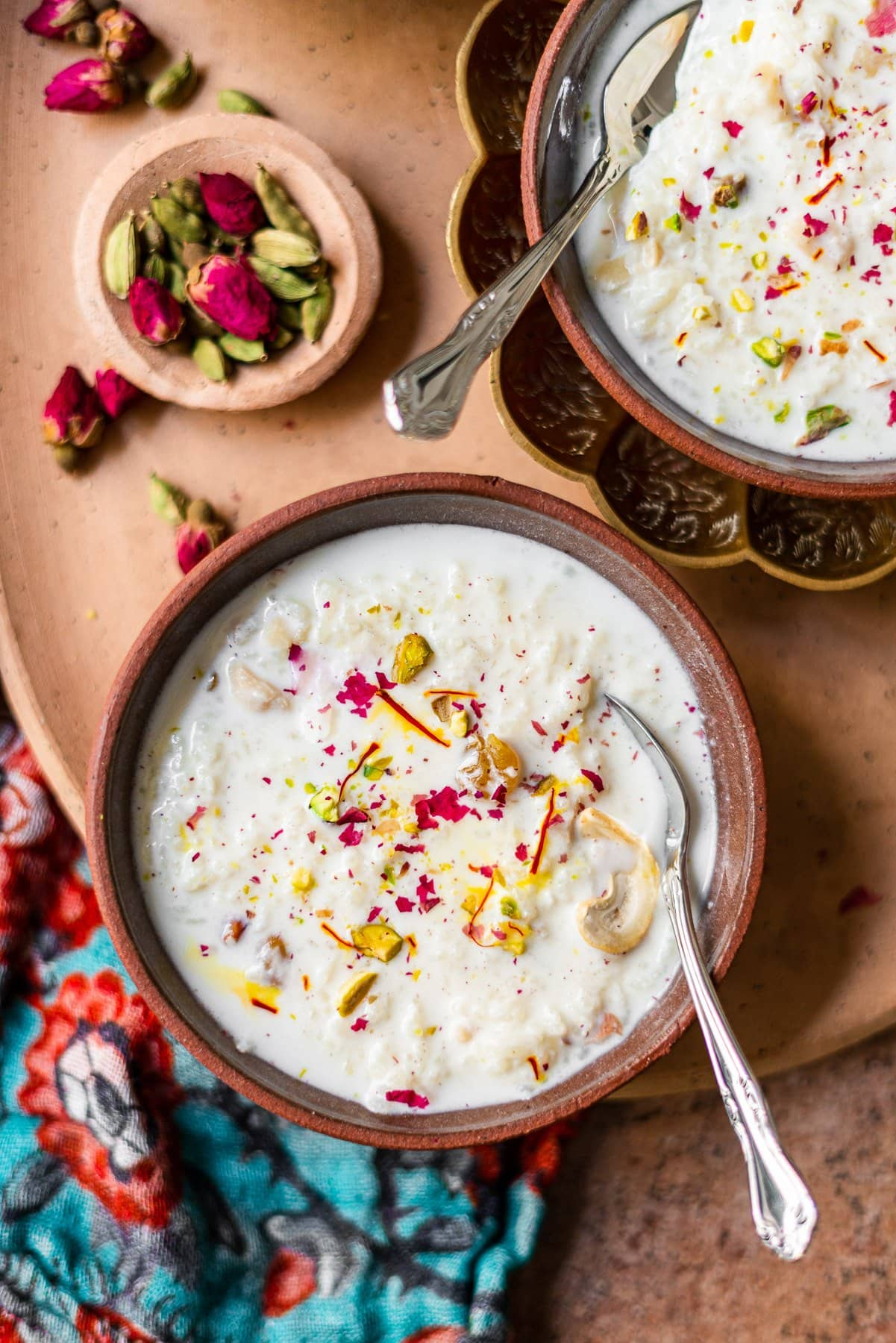bowl of kheer with spoon on a platter with cardamom and roses
