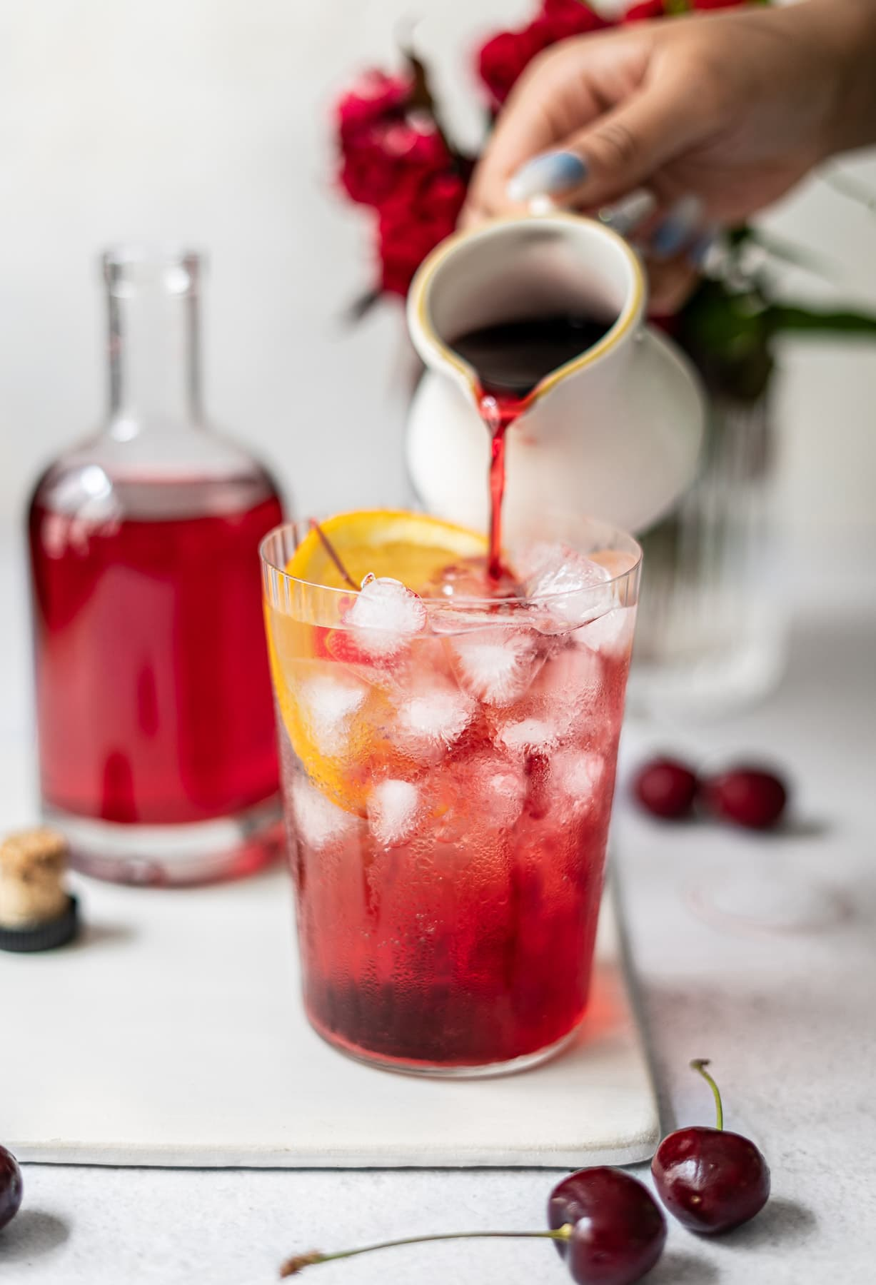 pouring homemade grenadine into a cup with an orange and ice
