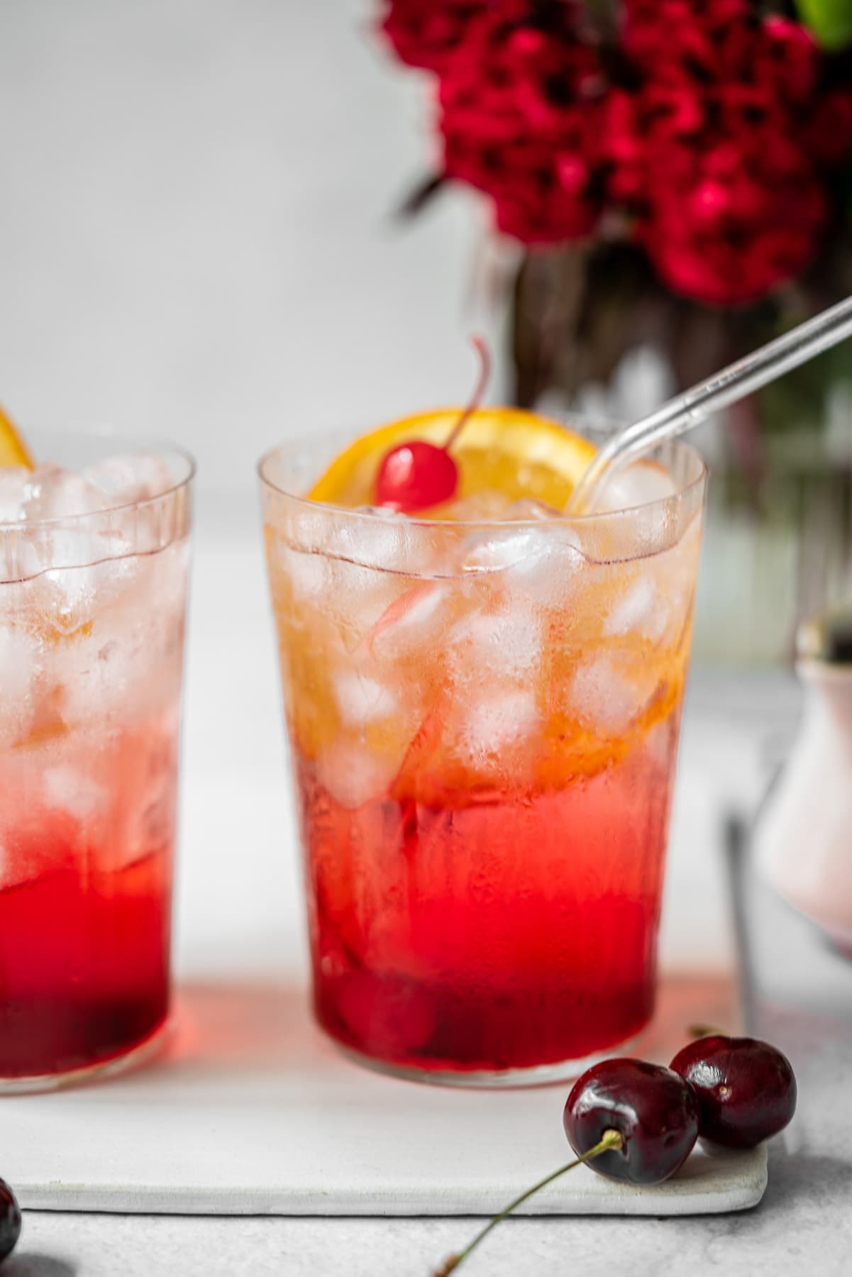 two glasses of shirley temple side by side with fresh cherries