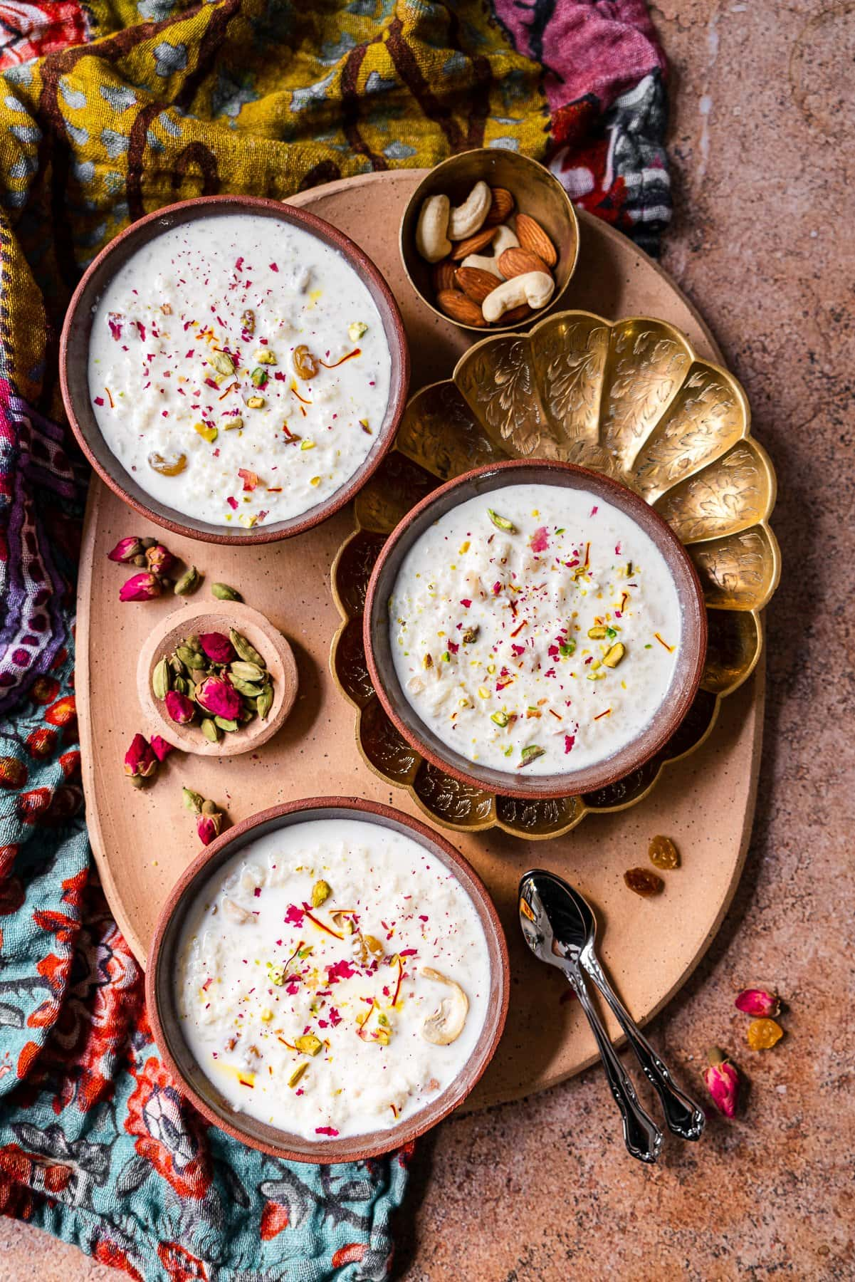a platter with three bowls of kheer, nuts, raisins, roses, and cardamom