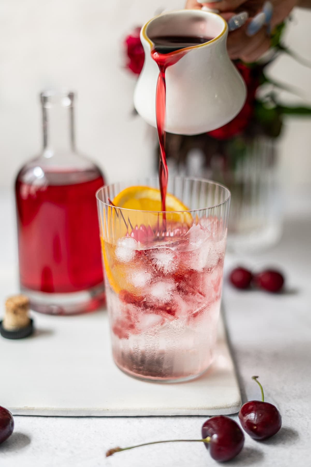 pouring grenadine into a cup with lemon lime soda