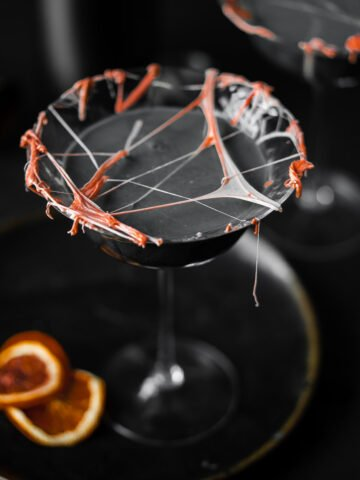 top shot of a coupe glass filled with a cocktail with marshmallow cob webs and dried blood oranges
