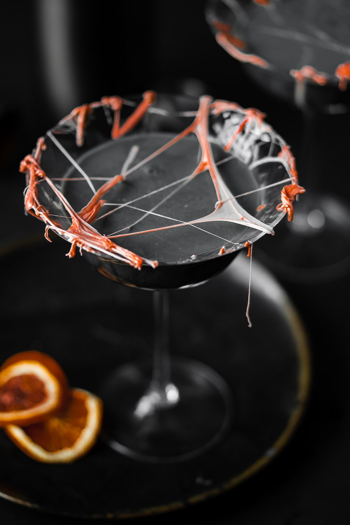 a coupe glass filled with a cocktail with marshmallow cob webs and dried blood oranges