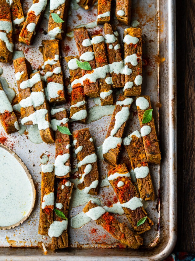 a tray full of chickpea fries garnished with curry leaf ranch on a wooden surface