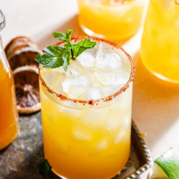 passionfruit margaritas on a tray with mint leaves