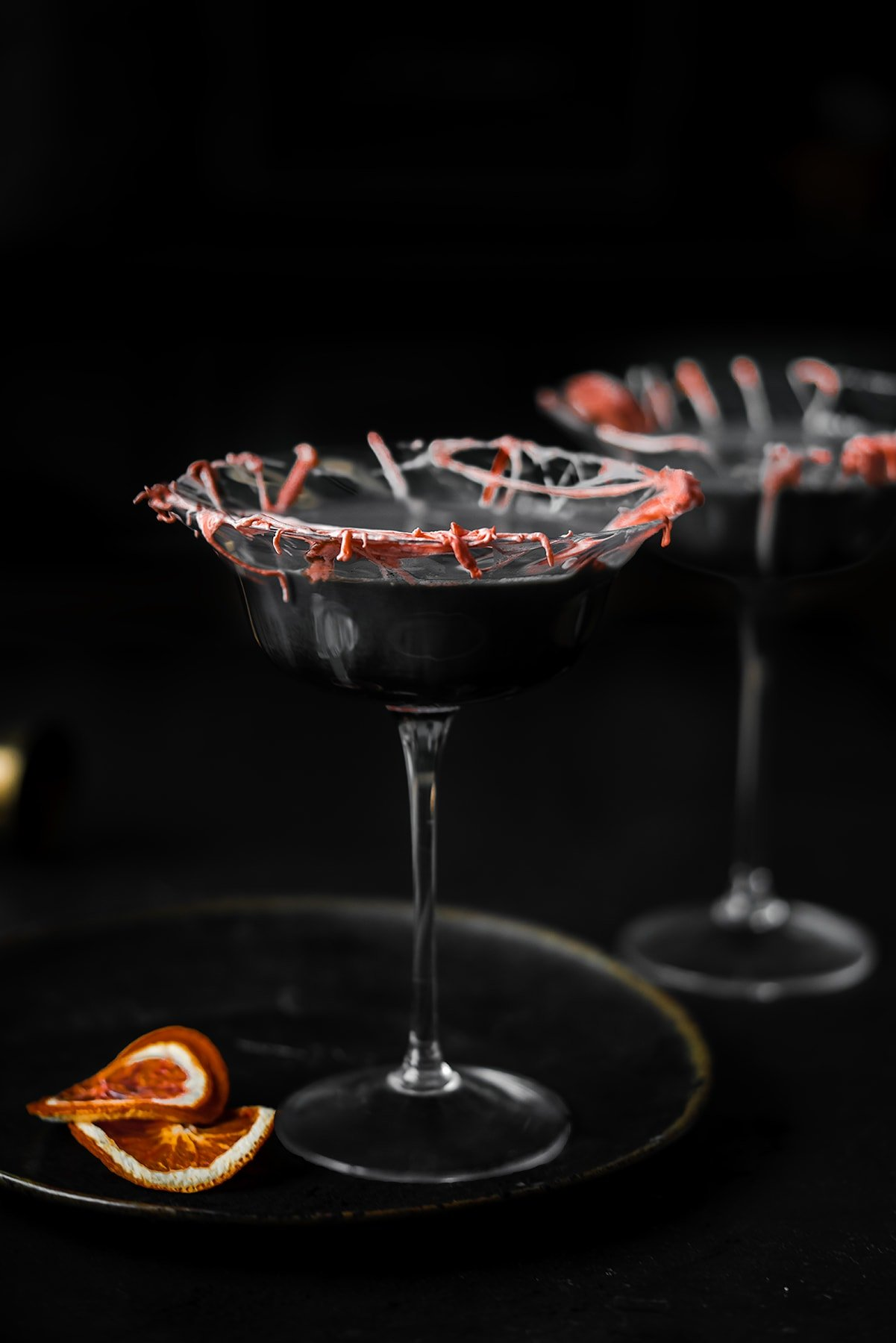 straight on shot of a coupe glass filled with a cocktail with marshmallow cob webs and dried blood oranges