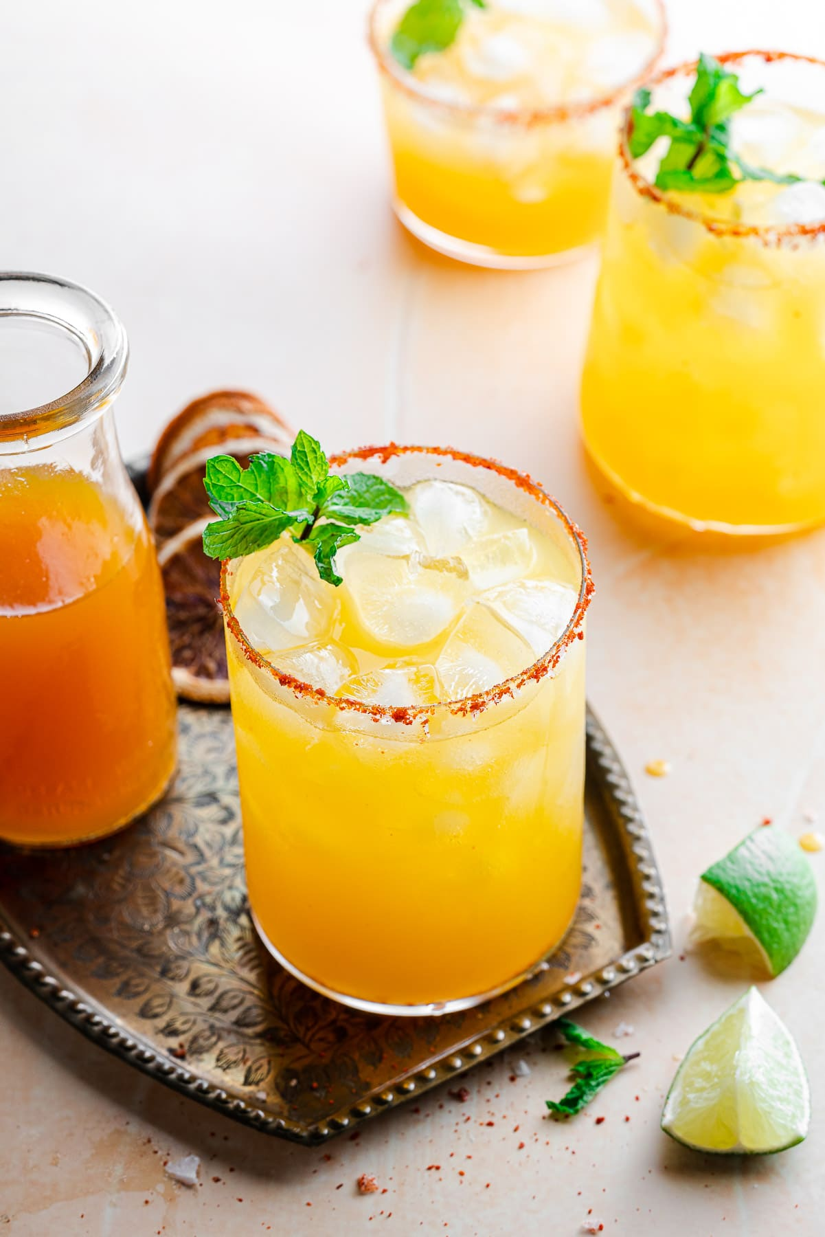 three passionfruit margaritas, one on a tray with passionfruit syrup and dehydrated blood oranges with mint leaves and lime wedges
