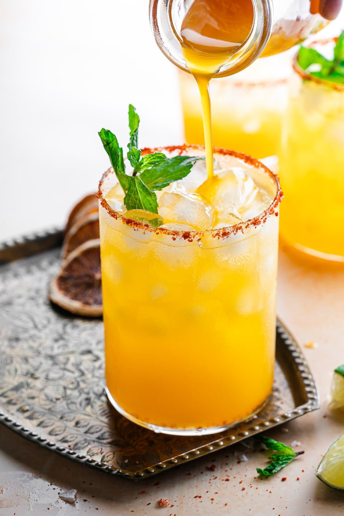 pouring passionfruit syrup into a passionfruit margarita