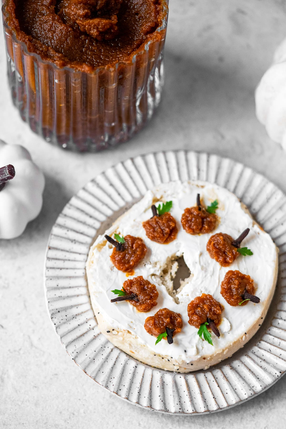 pumpkin butter cream cheese bagel on a plate with a jar of pumpkin butter